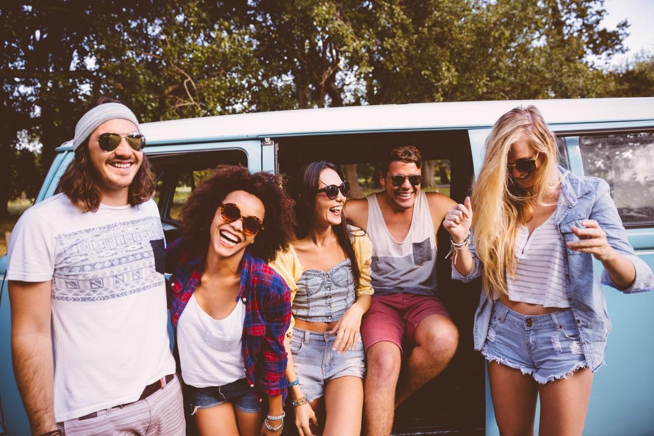 Amigos viajando juntos sorriem do lado de fora de uma kombi