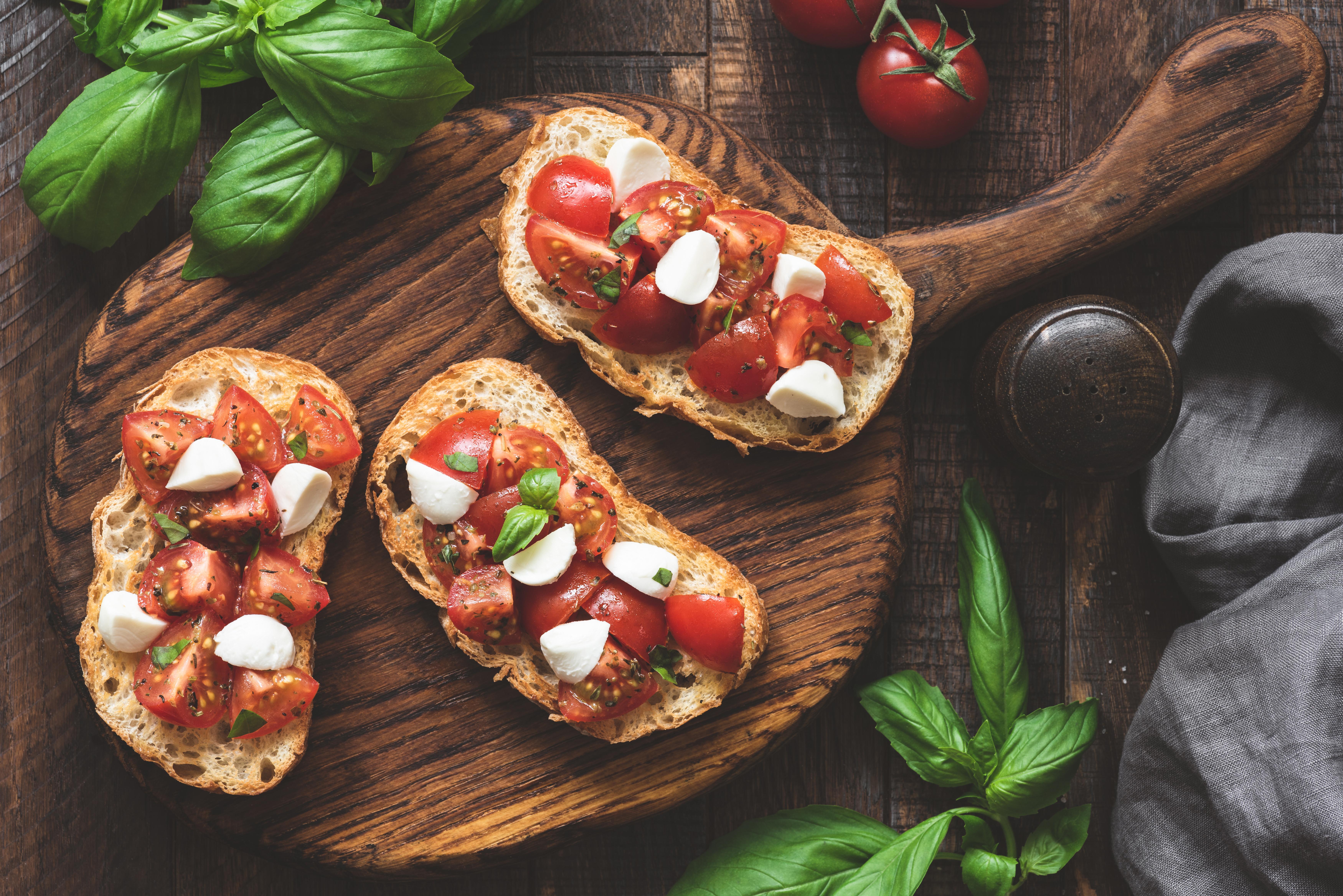 Italian bruschetta antipasti with tomatoes, mozzarella cheese and basil on wood board